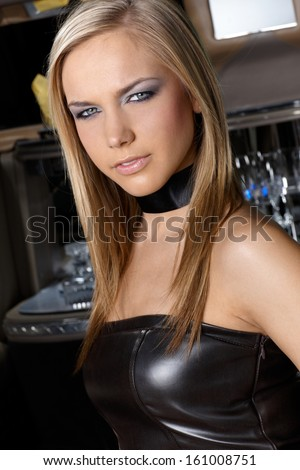Portrait of blonde young woman in leather evening dress.