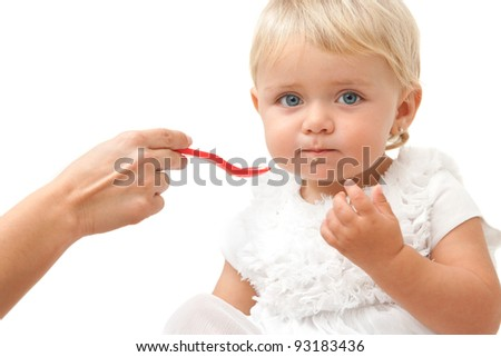 Portrait of blue eye baby girl being fed by hand with red spoon.Isolated on white background. - stock photo