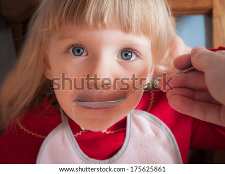 Portrait of blue eyed baby girl being fed by hand. Selective focus on eyes.  - stock photo