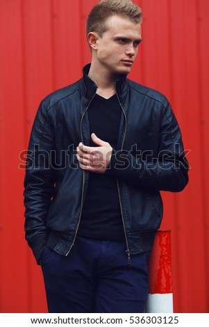 Portrait of blue-eyed young man with short blond hair wearing black leather jacket, posing over red urban corrugated background. Outdoor shot