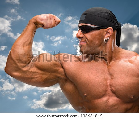 Portrait of bodybuilder towards a blue sky with clouds - stock photo