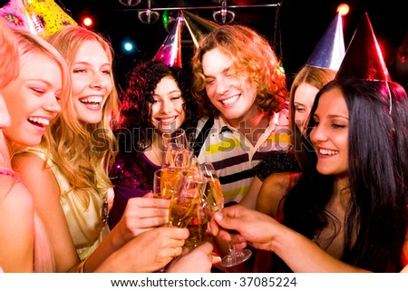 Portrait of boozing people in smart clothing toasting at birthday party