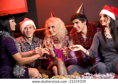 Portrait of boozing people wearing holiday clothing and toasting at xmas party