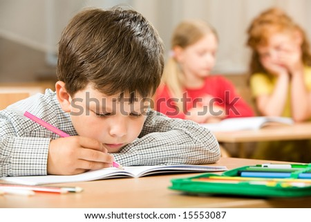 Portrait of bored pupil putting his head on desk and drawing something in copybook at lesson - stock photo