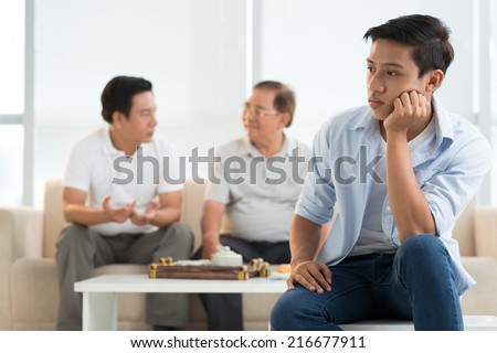Portrait of bored teenager and his father and grandfather talking in background - stock photo