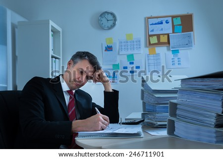 Portrait Of Boredom Mature Businessman With Stack Of Folders - stock photo