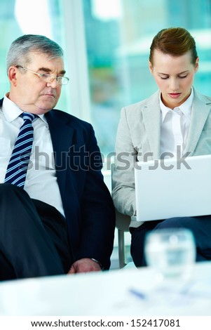 Portrait of boss looking at his employee working with laptop in office - stock photo