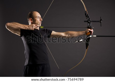 Portrait of bowman in black on black background aiming with bow and arrow, side view with focus on eyes.