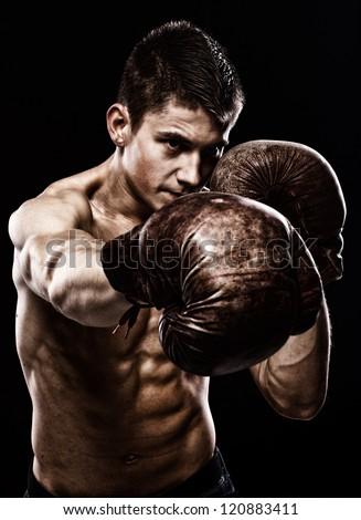 Portrait of boxer posing in studio in gloves - stock photo