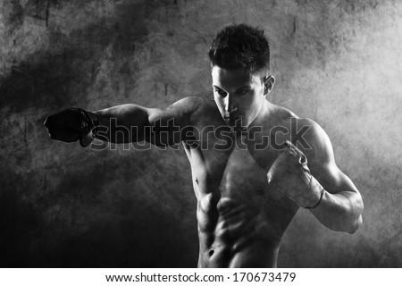 Portrait of boxer posing in studio in gloves .Photo has an intentional film grain) .Fine art. - stock photo