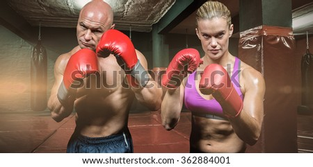 Portrait of boxers with gloves against red boxing area with punching bags - stock photo