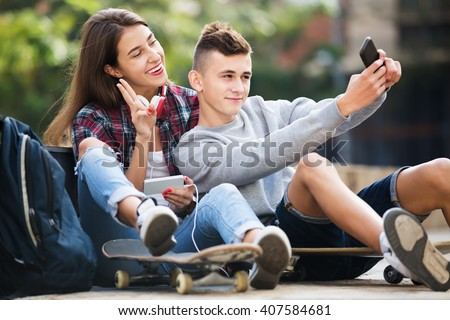 Portrait of boy and girl teens posing at mobile phone for selfie - stock photo
