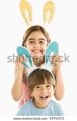 Portrait of boy and girl wearing rabbit ears smiling. - stock photo