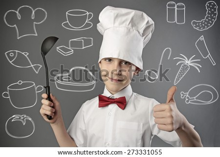 portrait of boy chef holding a ladle - stock photo