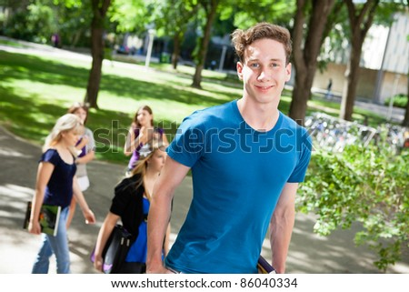 Portrait of boy going college with friends in background