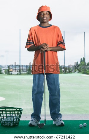 Portrait of boy golfing - stock photo