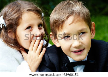 Portrait of boy groom looking aside with his bride telling him secret - stock photo