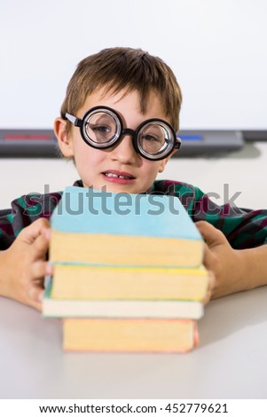 Portrait of boy holding books on table in classroom - stock photo