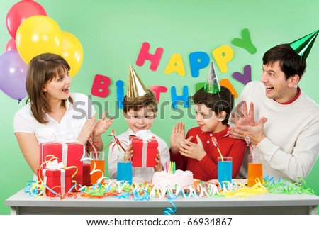 Portrait of boy holding his present with happy parents and brother near by - stock photo