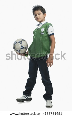 Portrait of boy holding soccer ball - stock photo