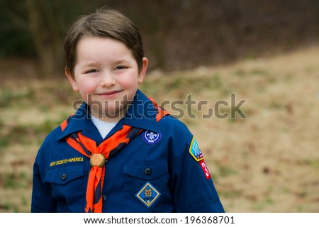 Portrait of boy in Cub Scout uniform outdoors - stock photo
