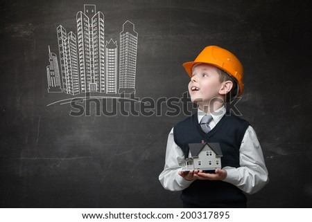Portrait of boy in hard hat keeping home model and looking at chalky drawing of buildings on grey background - stock photo