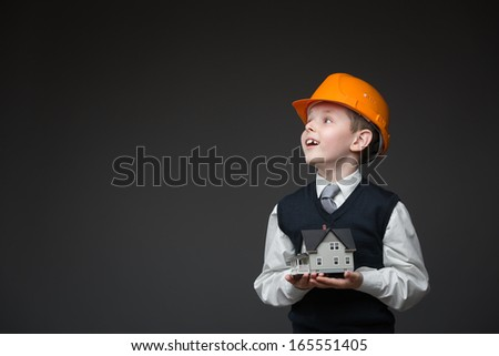 Portrait of boy in hard hat keeping home model on grey background - stock photo