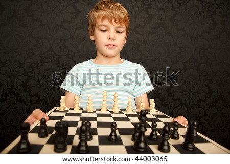Portrait of boy in T-shirt with chessboard against the wall with ornament.  Horizontal format. - stock photo