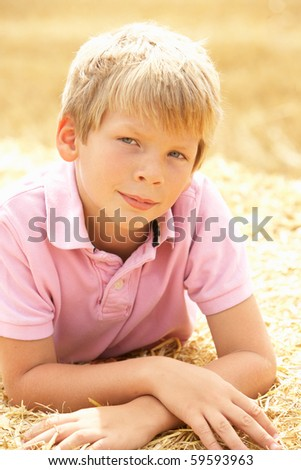 Portrait Of Boy Laying In Summer Harvested Field - stock photo
