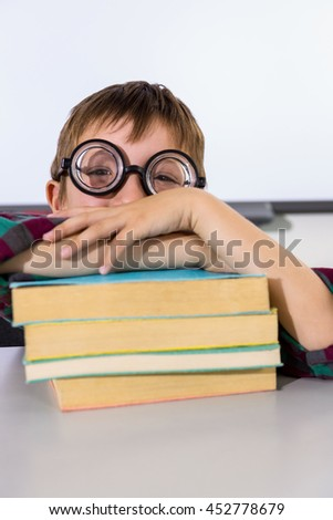 Portrait of boy leaning on books at table in classroom - stock photo