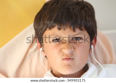 Portrait of boy looking angry as he plays a computer game wearing ear buds - copy space left - with shallow depth of field - stock photo