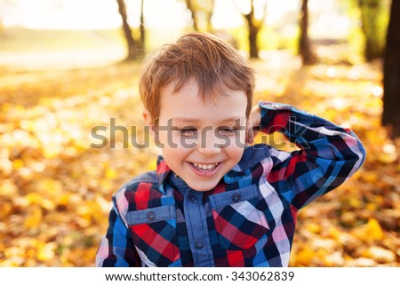 Portrait of boy playing in the park, shallow depth of field - stock photo