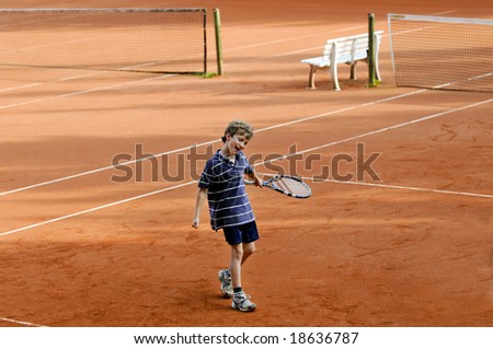 portrait of boy playing tennis - stock photo