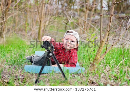 Portrait of boy playing with a toy shotgun outdoor - stock photo