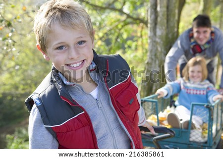 Portrait of boy pulling wheelbarrow, father and sister in background