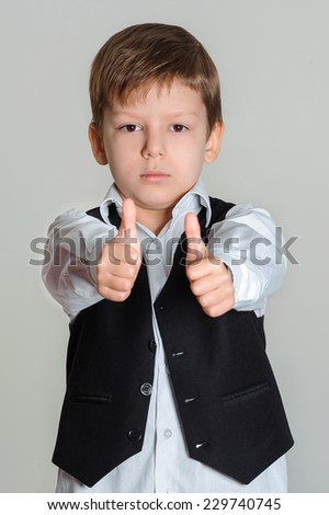 Portrait of boy showing thumbs up sign using both hands - stock photo
