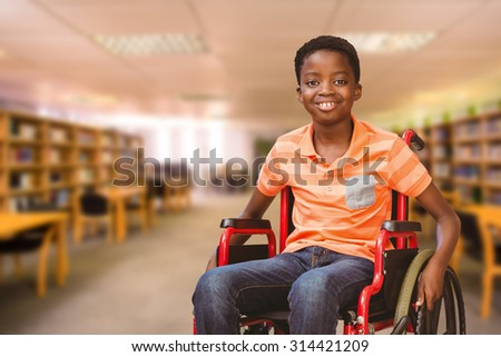 Portrait of boy sitting in wheelchair at library against view of library - stock photo