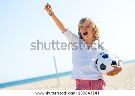 Portrait of boy standing on beach with soccer ball and winning attitude.