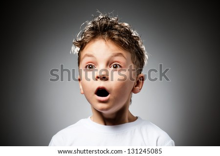 Portrait of boy surprised on gray background - stock photo