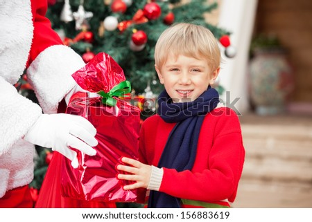 Portrait of boy taking Christmas gift from Santa Claus outdoors - stock photo