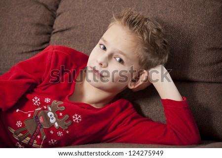 Portrait of boy wearing pajama on the sofa - stock photo