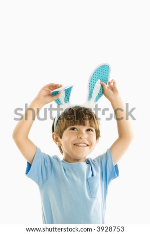 Portrait of boy wearing rabbit ears smiling. - stock photo