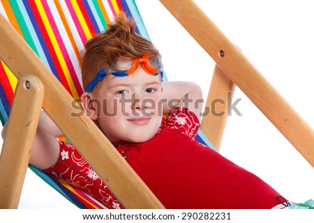 Portrait of Boy wearing swimming goggles sitting on beach chair. Isolated On White Background. - stock photo