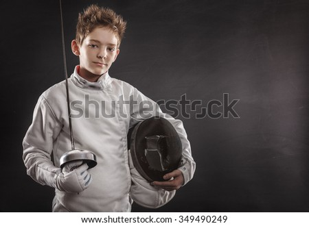 Portrait of boy wearing white fencing costume and black fencing mask - stock photo