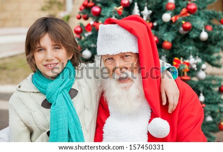 Portrait of boy with arm around Santa Claus against decorated Christmas tree outdoors - stock photo