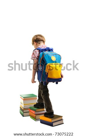 Portrait of boy with backpack walking from top to top of book piles - stock photo