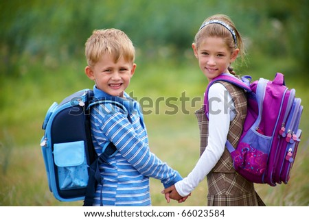 portrait of boy with girl walking to school along with rantsemi behind - stock photo