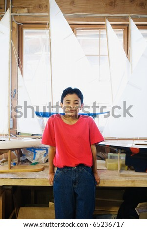 Portrait of boy with model sailboats in workshop
