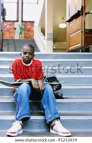 Portrait of boy with skateboard on school stairs - stock photo