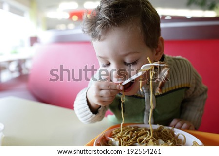 Portrait of boy with spaghetti in the restaurant - stock photo